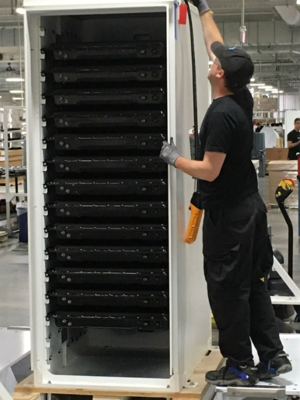 An assembly line employee prepares to move a Powerpack filled with battery trays.