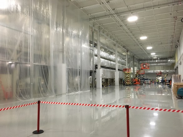 A long oven is used to bake the wet cathode paste onto a continuous sheet of aluminum foil. It runs along the entire back wall of the room and is partially covered in plastic sheeting on the left side. Another oven like it will be added to this room before production begins.