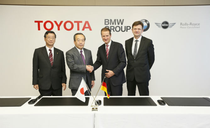 BMW and Toyota shake hands Jan. 2014 as they share costs on expensive advanced li-air battery and fuel cell research.