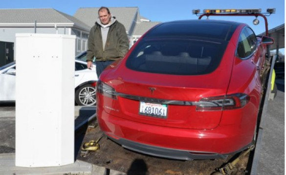A tow truck driver picks up a Model S. Journalist John M. Broder and Elon Musk exchanged words over this incident in 2013.