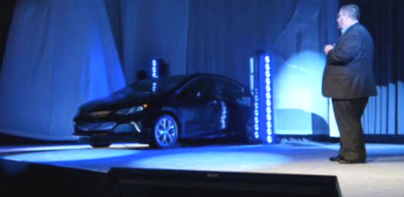 General Motors Volt marketing head Tim Mahoney stands back as the Volt is briefly revealed.